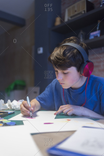Beginner artist listening music with headphones while painting with colors