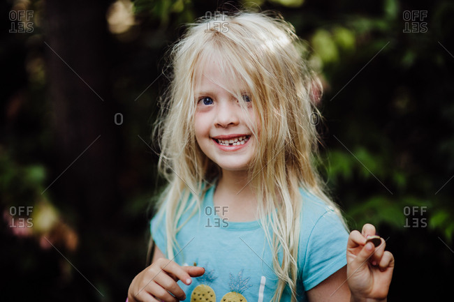 Girl showing a coin from the tooth fairy after losing her first tooth