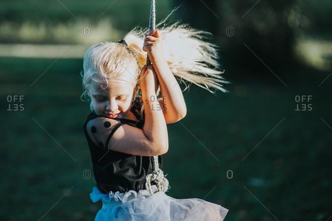 Girl swinging on a rope swing