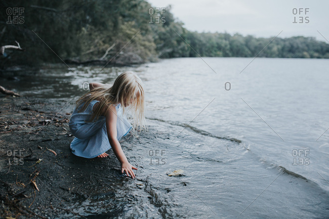 Girl sitting near a lake playing with water