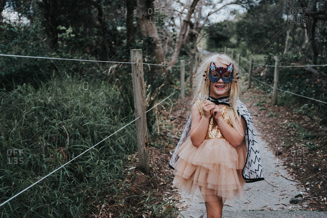 Girl wearing a cat mask standing on a footpath outside