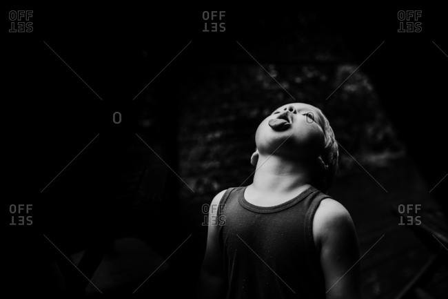 Boy catching raindrops with his tongue