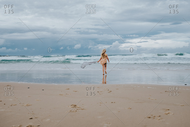 Girl wading in the water on the beach on a windy day