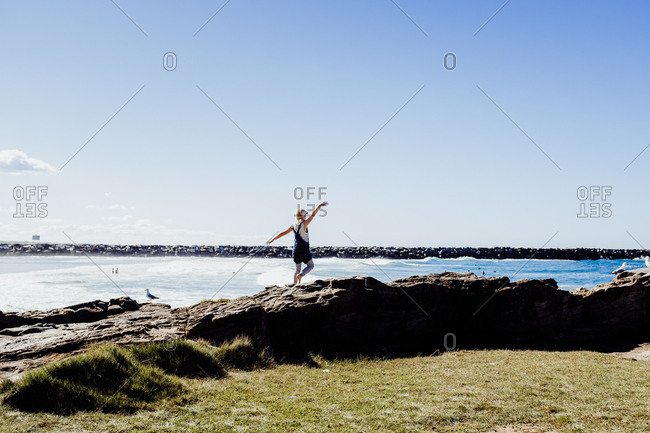 Girl walking on rocks at the beach