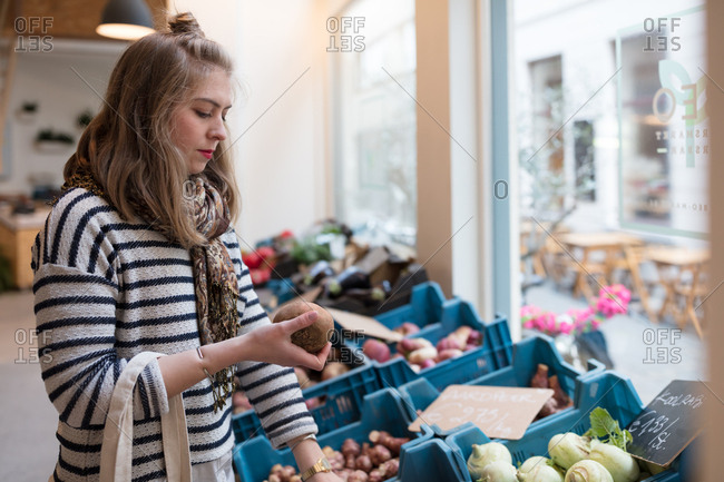 Young woman buying vegetables at organic market
