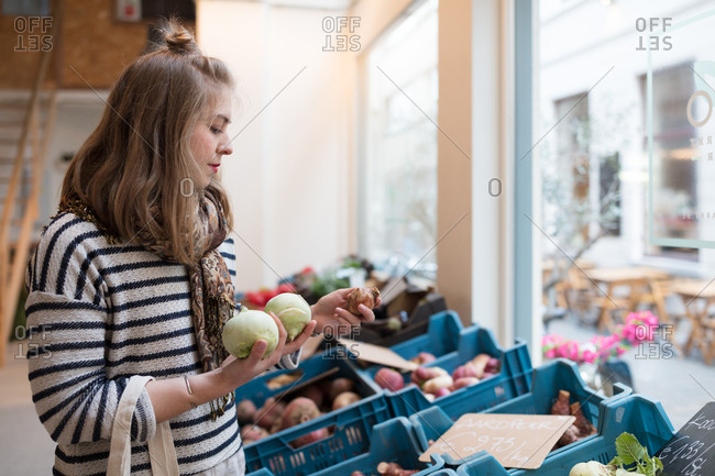 Woman buying fresh vegetables in organic store