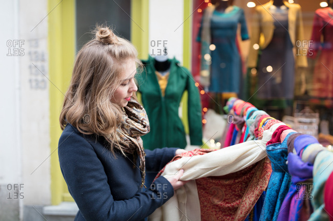 Young woman shopping scarves on street shop