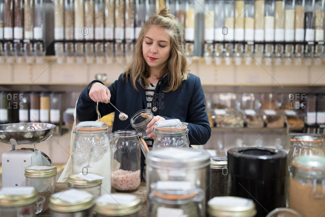 Young woman pouring seeds into jar in a small organic grocery store