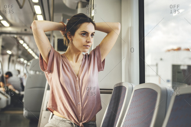 Young woman sitting in train carriage tying hair up looking out of window