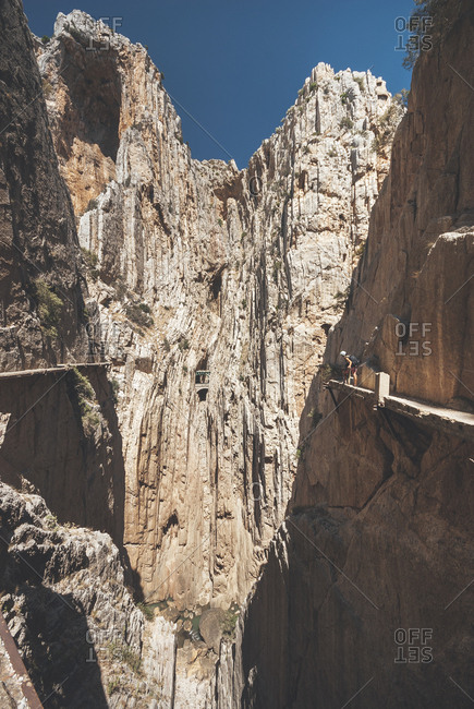 A hiker looking down over edge on the narrow path around the Caminito del Rey gorge in Malaga, Spain