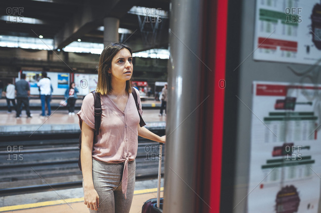 Young woman standing on train station platform checking schedule on board