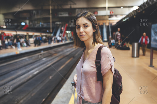 Portrait of young woman waiting for train at platform
