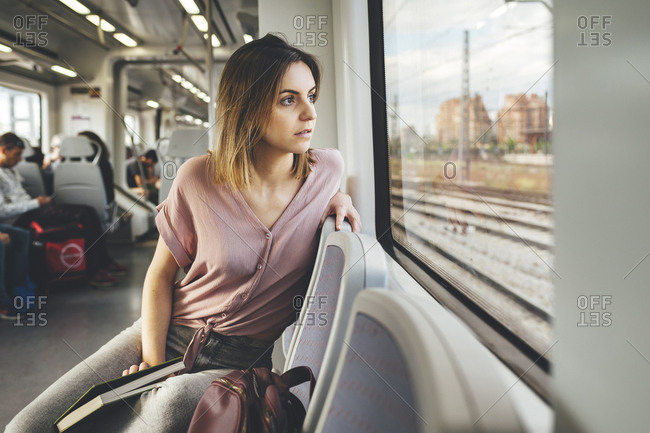 Young woman turning in seat to look out of train window