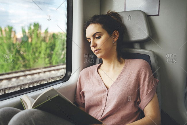 Young woman passing time reading book in train