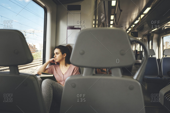 Young woman looking at passing landscape out of window while traveling on train