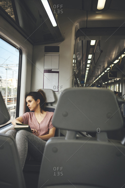 Young woman checking approaching station stop out of window while traveling on train