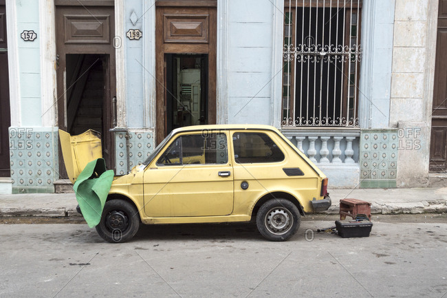 Havana, Cuba - March 07, 2015: A small broken down vintage car undergoing repairs by the side of the street