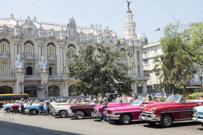 Havana, Cuba - March 21, 2015: Colorful vintage American cars parked in front of the ornate Grand Theater building
