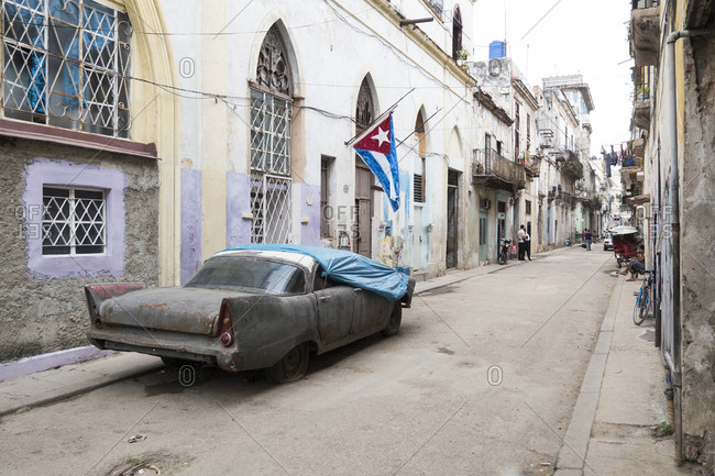 Havana, Cuba - March 25, 2015: Derelict antique car covered in tarp parked in residential street