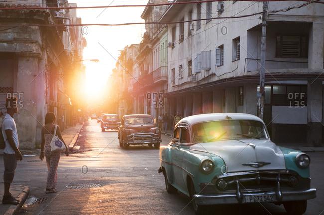 Havana, Cuba - March 27, 2015: Setting sun back lighting antique American cars driving down street