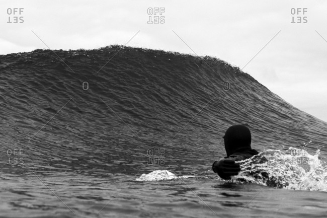 Lone surfer paddling out past peak of a wave in cold water wearing wetsuit