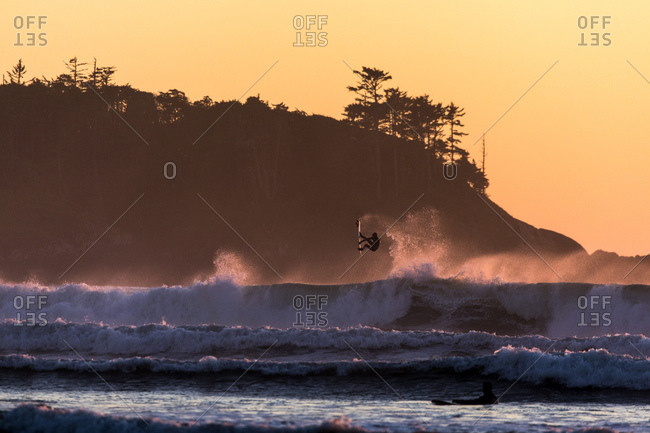 Setting sun highlighting surfer performing aerial move with coastline in background