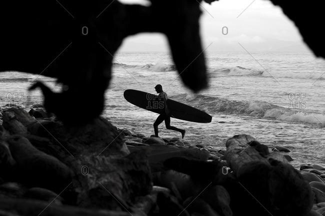 Surfer carrying long board hopping over rocks while leaving the ocean