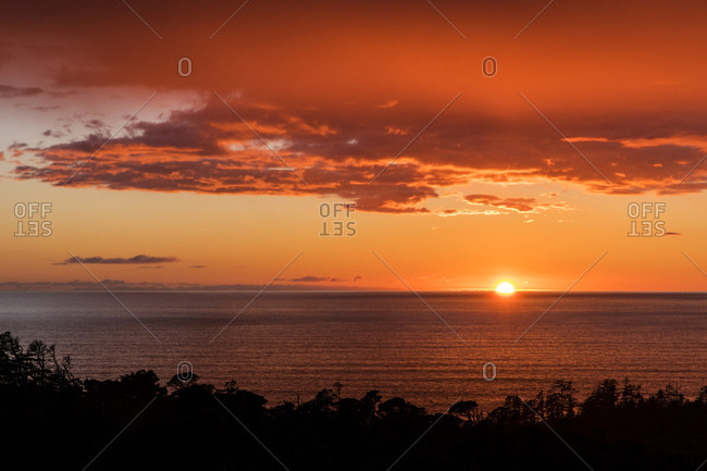 Looking over coastal forest as sun drops into the ocean and clouds glow