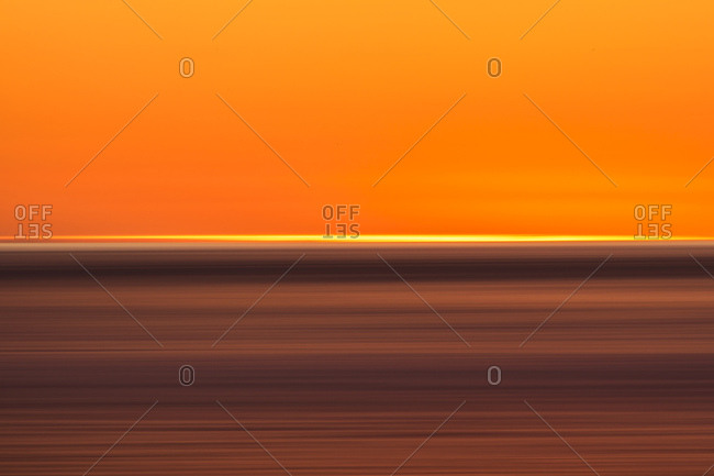 Abstract image of lines of gold and orange caused by setting sun over the ocean