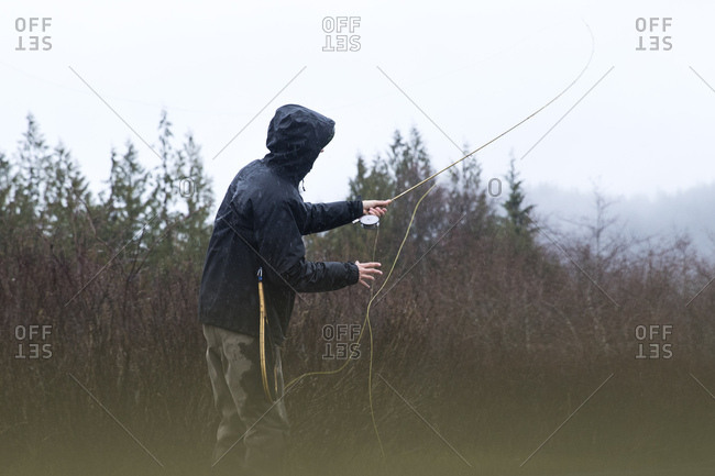 Rearview of fly fisherman casting on overcast and rainy day