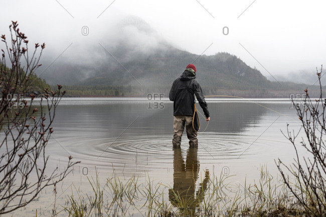 Rearview of fly fisherman standing in still waters of lake with mist shrouding hill side in distance