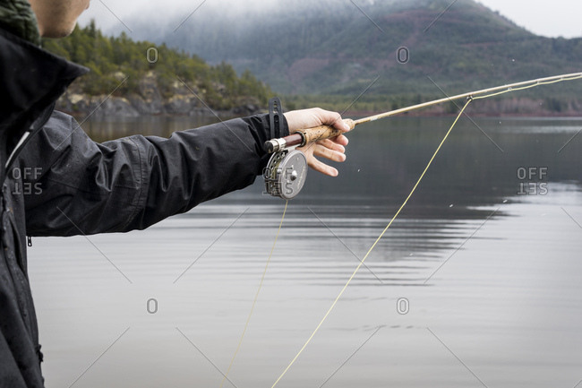 Close up of fly fisherman balancing rod in hand after casting fly