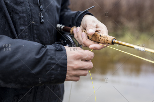 Close up of fly fisherman slowly drawing in line over finger after casting