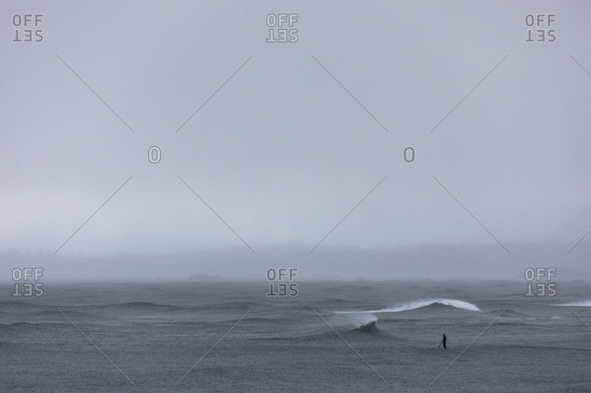 Lone stand up paddle boarder paddling out to sea on grey and overcast day