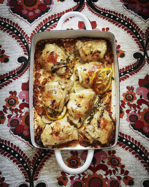 Seven pieces of chicken in a baking pan with lemon