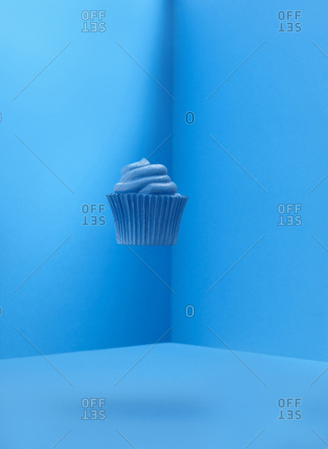Blue cupcake floating in a blue space