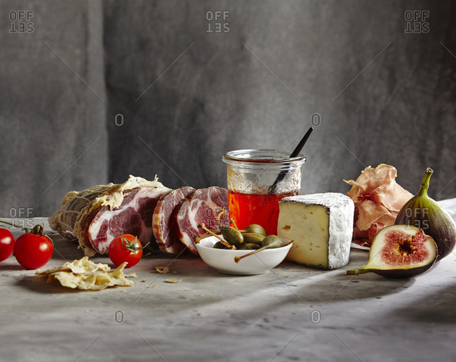 Food still life with cured meat, cheese, figs, olives, tomatoes and preserves