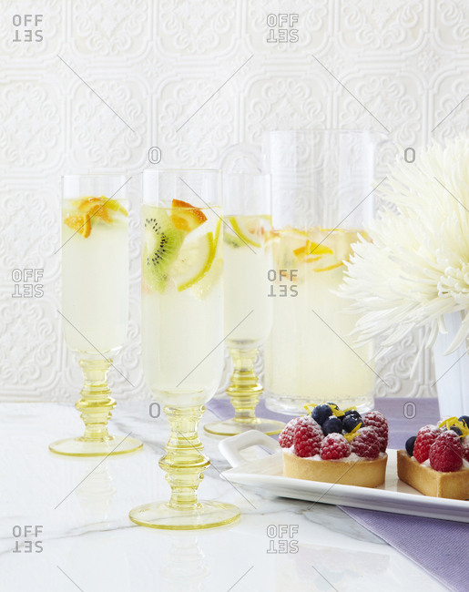 Collection of sparking drinks with fruit and tarts