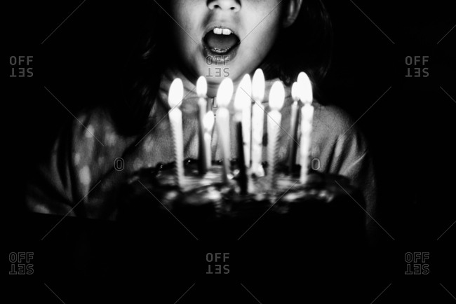 Girl blowing out birthday candles in black and white