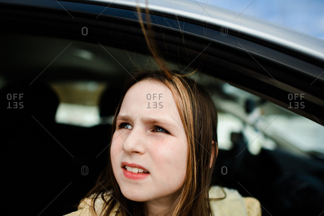 Girl riding in car with wind blowing her hair around