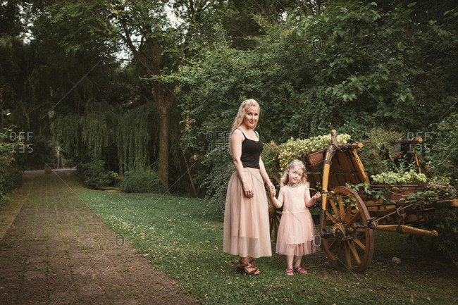 Mother and daughter standing next to wooden cart