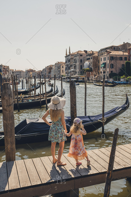 Mother and daughter standing on a dock on a canal in Venice, Italy