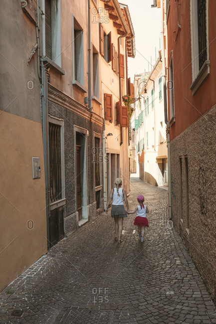 Mother and daughter walking down cobblestone street in Venice, Italy
