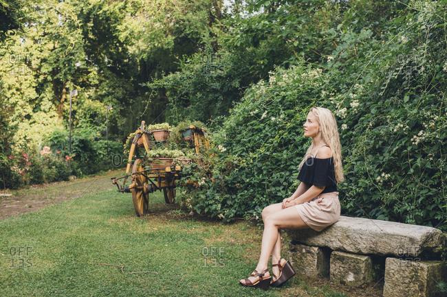 Woman sitting on stone garden bench