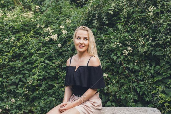 Blonde woman sitting on stone garden bench