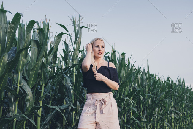 Woman standing in front of a corn field