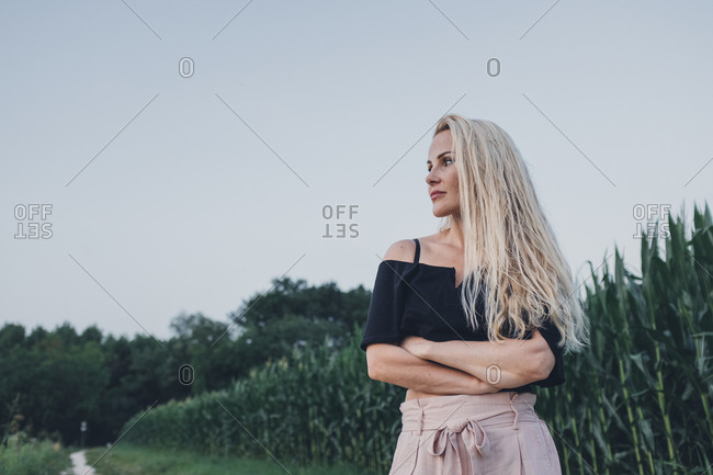 Blonde woman standing in front of a corn field with her arms crossed