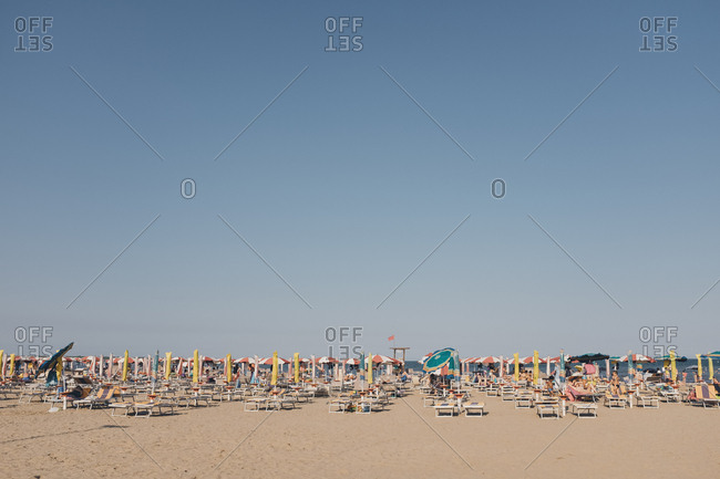 Caorle, Italy - July 10, 2017: Beach filled with lounge chairs and umbrellas