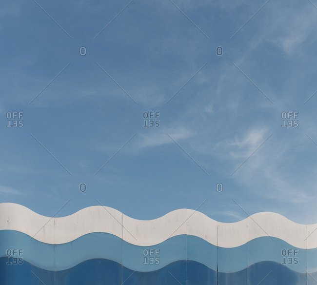 Blue and white waves against a blue sky