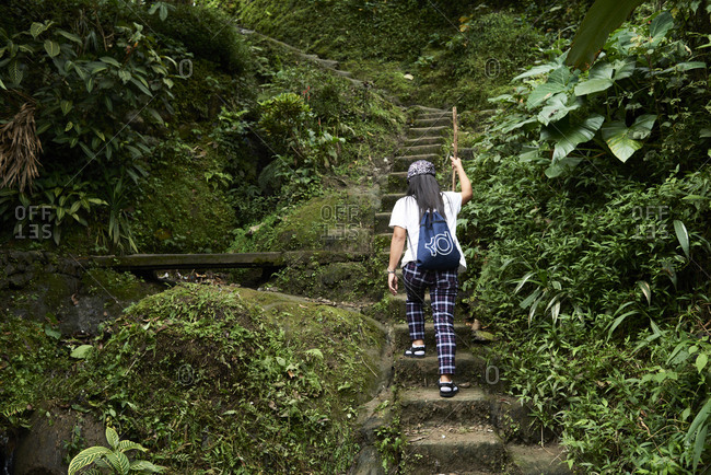 Batad, Philippines - March 3, 2018: Filipina tour guide going up stairs into the jungle with walking stick.
